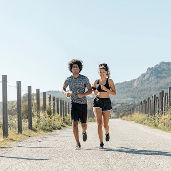 Young couple in sportswear running along road
