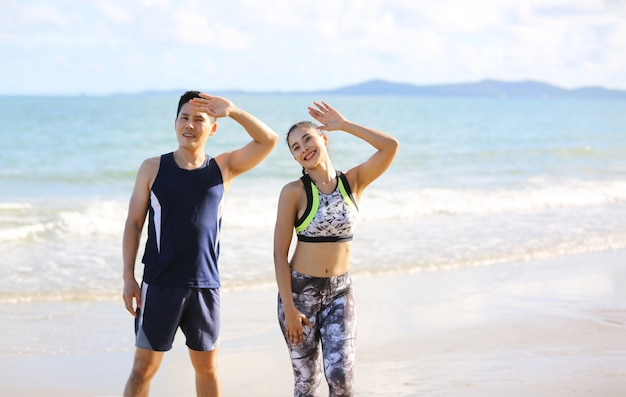 Young couple in sportswear standing and exercise body on the beach in morning.