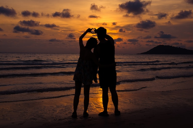 Young couple stand on beach with sunset