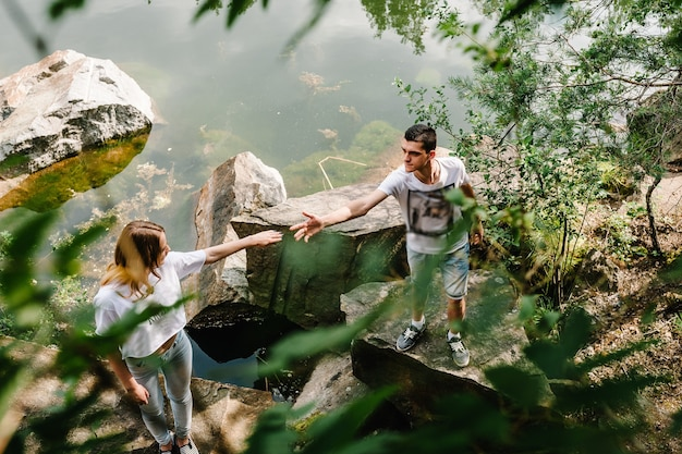 Молодая пара стоит на камне у озера
