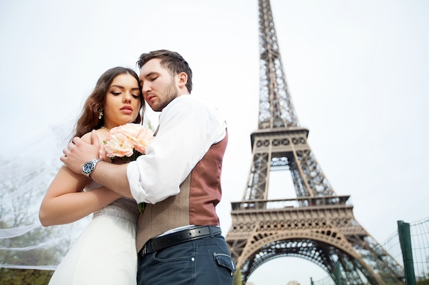A young couple standing against the eiffel tower