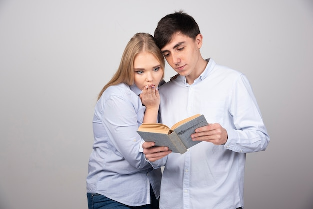 회색 벽에 서서 책을 읽는 젊은 부부