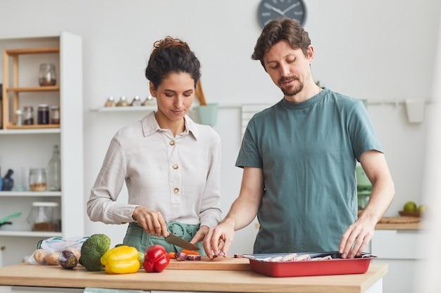 台所のテーブルに立って、自宅の台所で一緒に夕食を準備している若いカップル