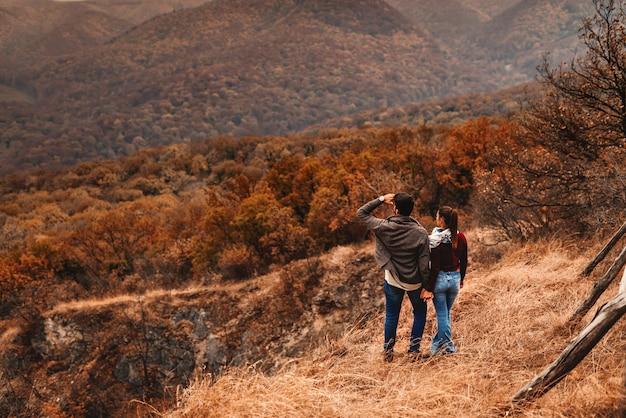 若いカップルが視点に立って、景色を楽しみます。手を繋いでいるカップル。秋の時間。