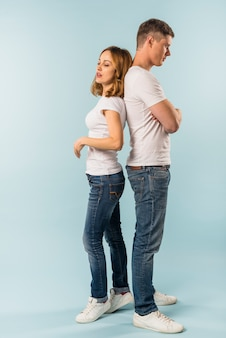 Young couple standing back to back against blue background
