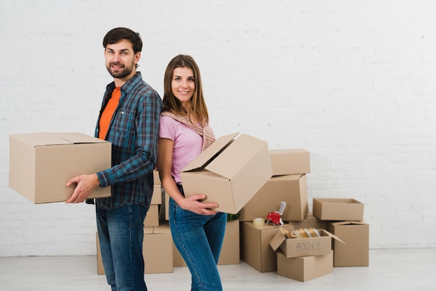 Young couple standing back to back holding cardboard boxes in hand