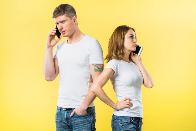 Young couple standing back to back talking on cell phone against yellow background