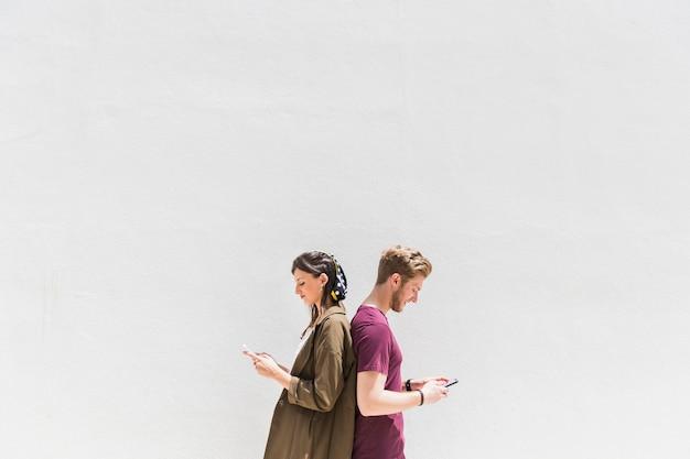 Молодая пара стоял спиной к спине с помощью мобильного телефона