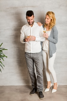 Young couple standing by wall and holding glasses of white wine in hands