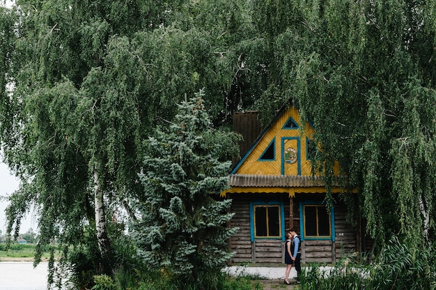 Молодая пара стоит, обниматься и целоваться возле старого дома на острове в лесу