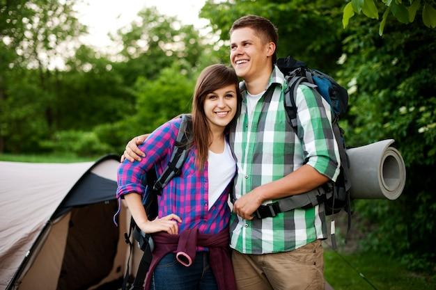 テントの前に立っている若いカップル