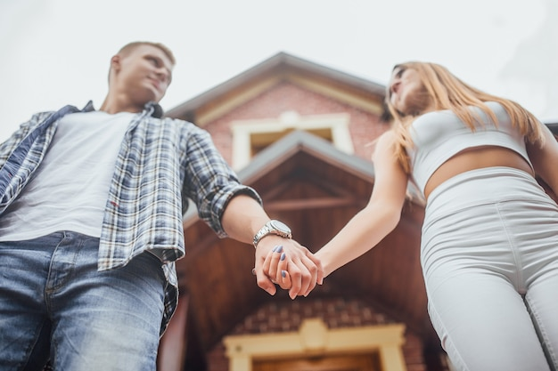 家の前に立って、手で自分自身を保持している若いカップル