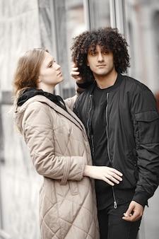 コートを着て通りに立っている若いカップル。