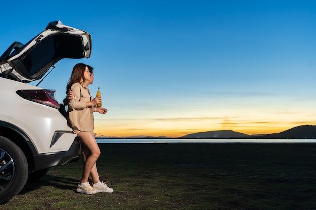 日没時に野原で楽しんでいる車の近くに立っている若いカップル