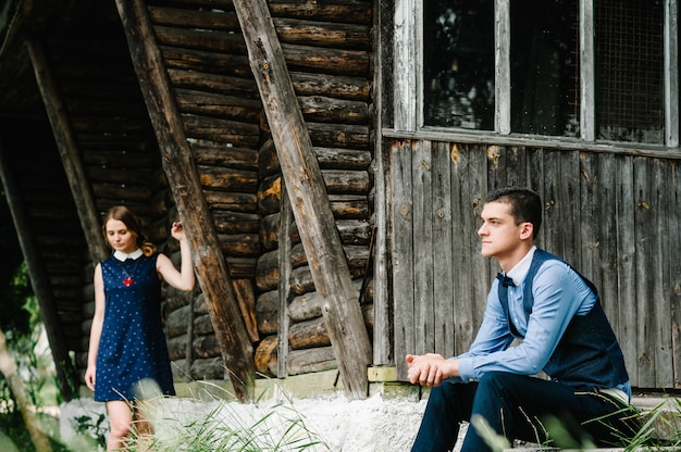 Young couple standing near an old wooden stylish house