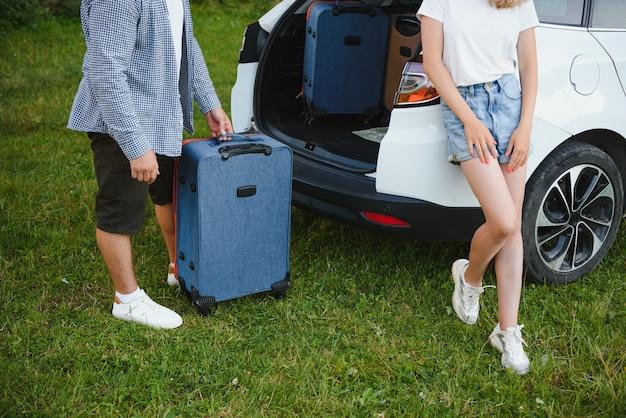 Молодая пара, стоящая возле открытого багажника автомобиля с чемоданами, глядя в камеру, на открытом воздухе