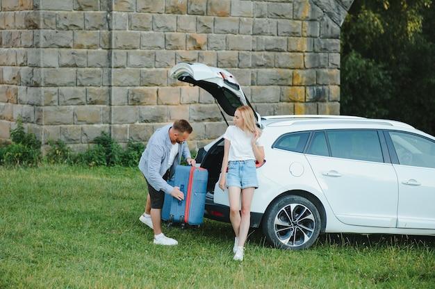 야외에서 카메라를 바라보며 가방을 들고 열린 자동차 부츠 근처에 서 있는 젊은 부부