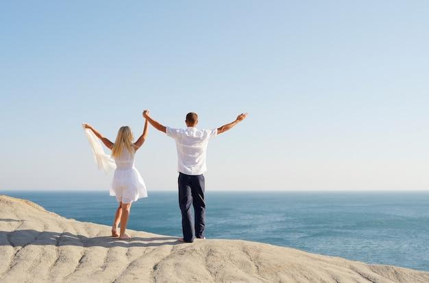 Молодая пара стоя на скале и подняла руки к небу