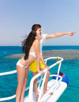 화창한 여름날 요트 코에 서 있는 젊은 부부, 소년은 손으로 가리키고, 머리카락이 자라는 바람, 배경에 아름다운 청록색 바다
