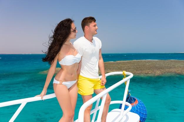 화창한 여름날 요트 코에 서 있는 젊은 부부, 머리카락이 자라는 바람, 배경에 아름다운 청록색 바다