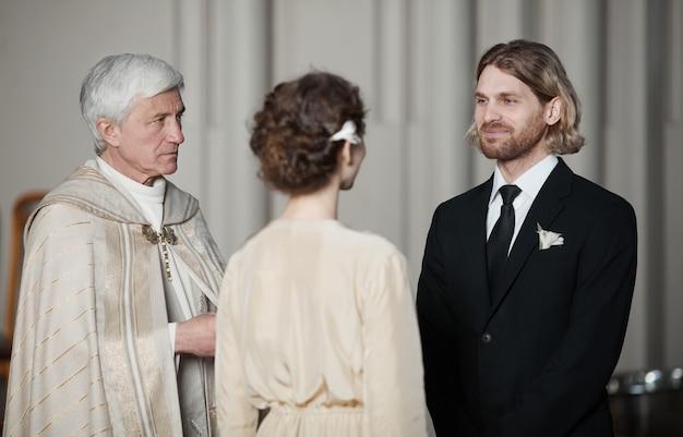신부와 함께 결혼식에서 서로 반대편에 서서 기도하는 젊은 부부