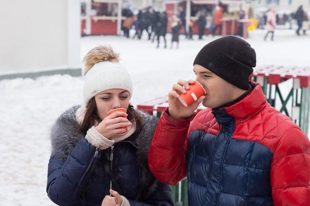 冬の雪の中で都会の広場に屋外に立っている若いカップルは、持ち帰り用のコップから寒い日にホットドリンクを飲み、遠くを歩いている人々