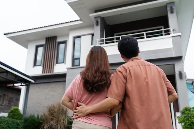Молодая пара стоит снаружи и смотрит в свой дом