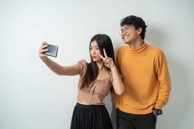 Young couple standing and selfie using a smart phone