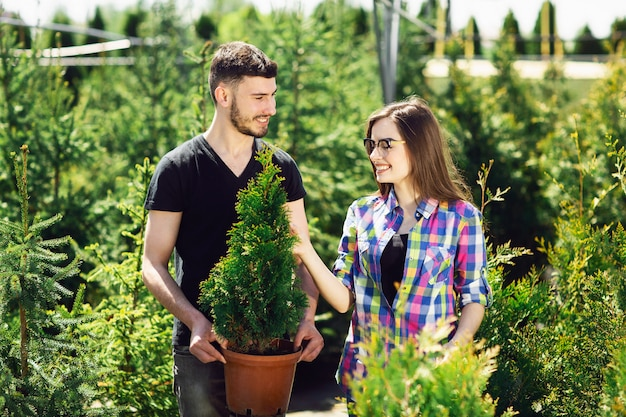Young couple standing together, holding a pot with a small fir tree and looking at a plant