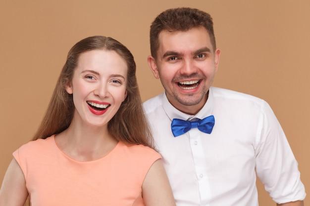 Молодая пара стоя вместе, глядя в камеру с зубастой радостной улыбкой