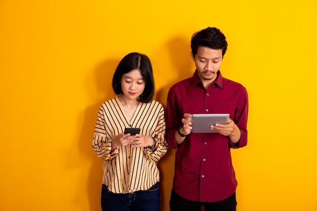 Молодая пара стоит, держа телефон