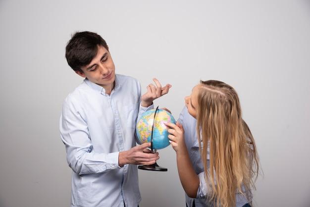 Giovane coppia in piedi con un globo terrestre su un muro grigio