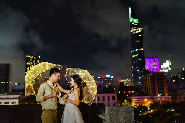 Young couple standing with led light umbrella in dark
