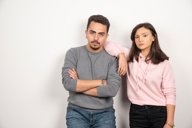 Young couple standing with serious expression.