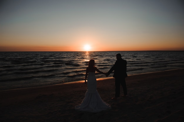 Young couple stands at the sea beach looking at sunset.