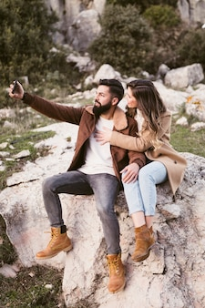 Young couple staying on a rock and taking a selfie