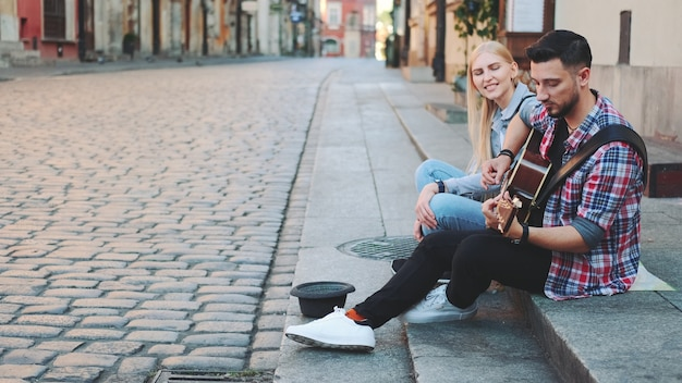 Young couple of street singers in old part of the city sitting on sidewalk. man playing guitar and woman singing.