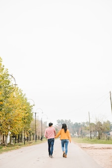 Young couple strolling along road