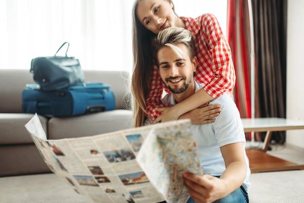 Молодая пара изучает карту перед летним путешествием
