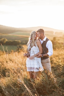 Young couple in stylish boho rustic clothes embracing, standing in the field at sunset