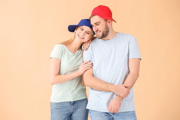 Young couple in stylish caps on color background