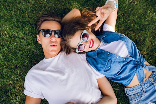 Young couple in sunglasses is lying on grass in park. girl with long curly hair is lying on shoulder of handsome guy in white t-shirt.  they aping to camera. view from above.