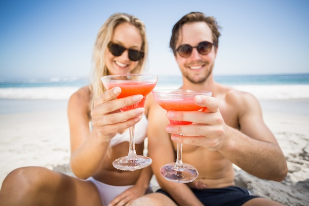 Young couple in sunglasses showing cocktail glass on the beach