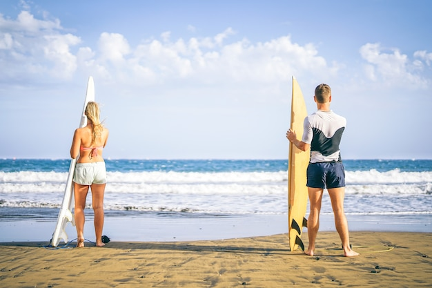 Young couple of surfers standing on the beach with surfboards preparing to surf on high waves