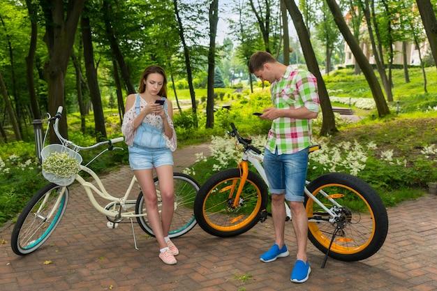 公園で自転車に寄りかかってスマートフォンでインターネットサーフィンをしている若いカップル