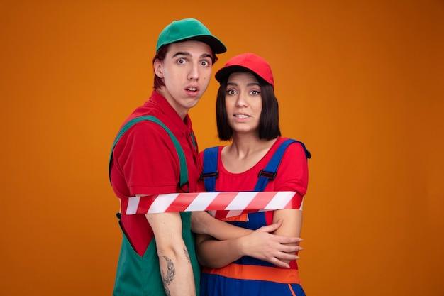 Giovane coppia sorpresa ragazzo ragazza all'oscuro in uniforme da muratore e berretto legato con nastro di sicurezza ragazza tenendo le mani incrociate sulle braccia entrambi