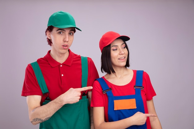 Young couple surprised guy joyful girl in construction worker uniform and cap pointing at side guy looking at camera girl looking at side isolated on white wall