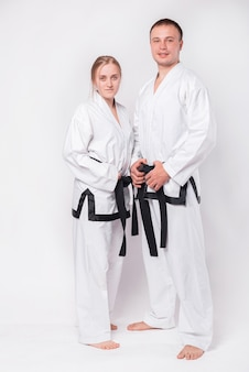 Young couple in taekwondo uniform on white
