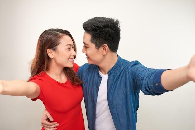 若いカップルは白い背景でselfieを取る