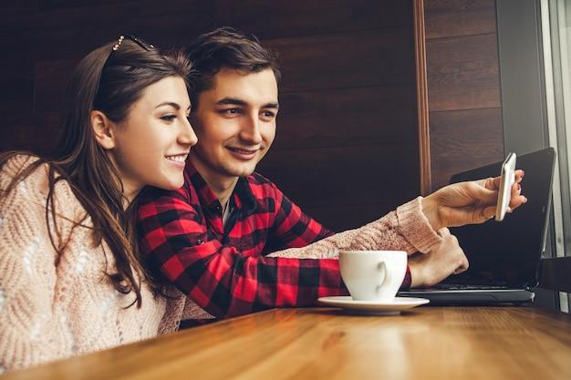 Молодая пара делает селфи и пьет кофе в кафе, используя ноутбук перед окном